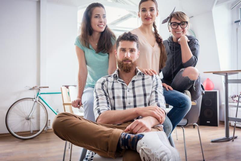 Fyra medarbetare som bär tillfällig kläder under arbete i ett modernt nav royaltyfri bild