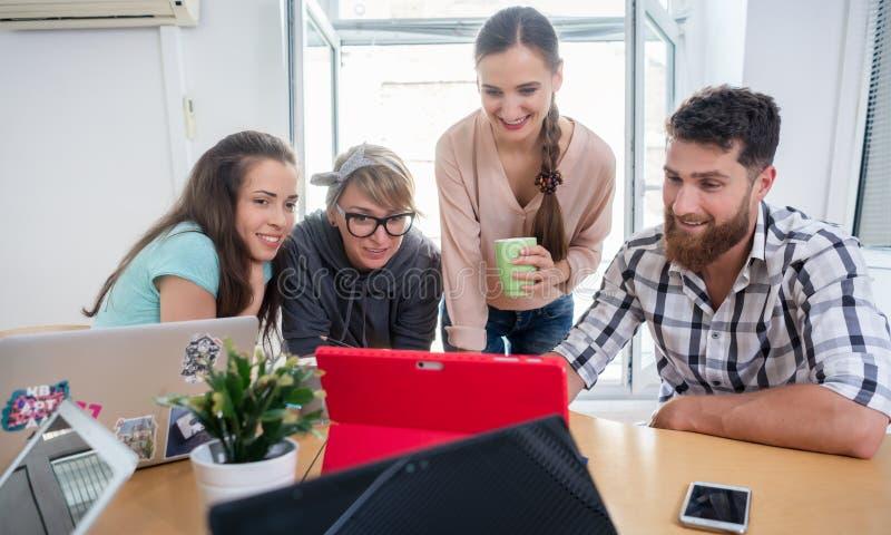 Fyra medarbetare som håller ögonen på en affärspresentation i ett modernt delat kontor royaltyfria foton
