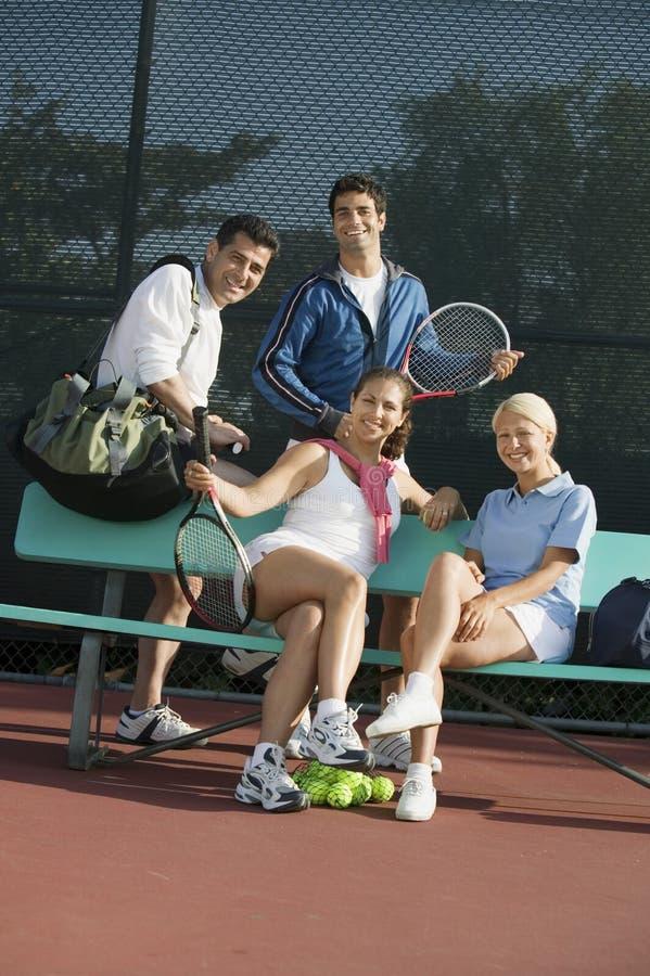 Fyra mixedtennisspelare på bänken på tennisbanaståenden royaltyfri fotografi