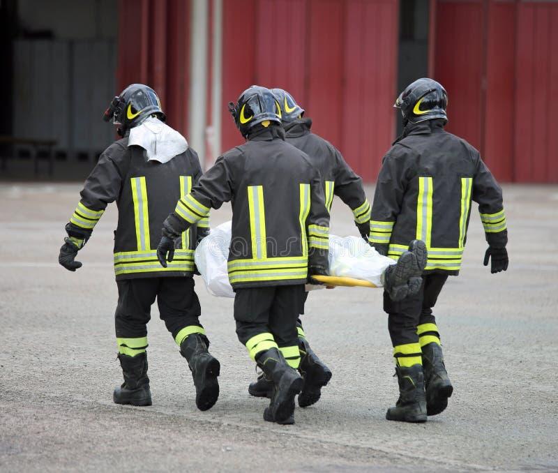 Fyra modiga brandmän transporterar det sårat med en bår royaltyfria bilder