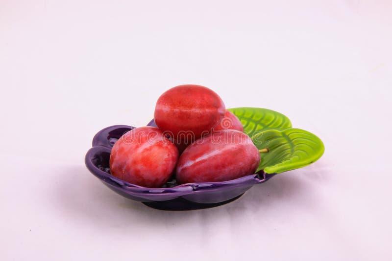 Fyra mogna röda plommoner på en liten maträtt i studio royaltyfri bild