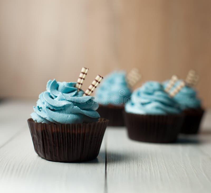 Fyra muffin med blått lagar mat med grädde i form för brunt papper royaltyfria bilder