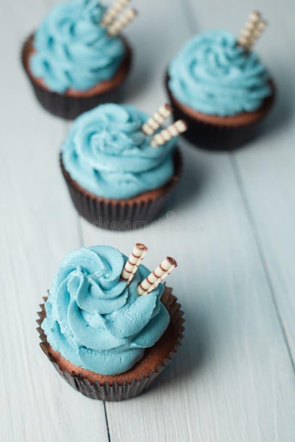 Fyra muffin med blått lagar mat med grädde i form för brunt papper royaltyfri bild
