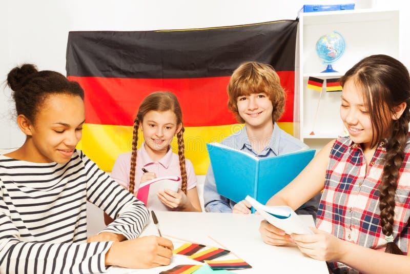 Fyra multietniska studenter som studerar tysk på grupp royaltyfri foto