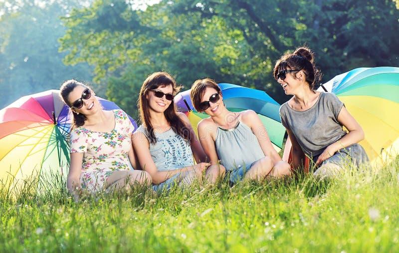 Fyra nätta flickvänner som rymmer färgrika paraplyer arkivbilder