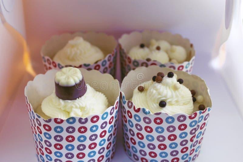 Fyra nya smakliga vaniljmuffin i en ask fotografering för bildbyråer