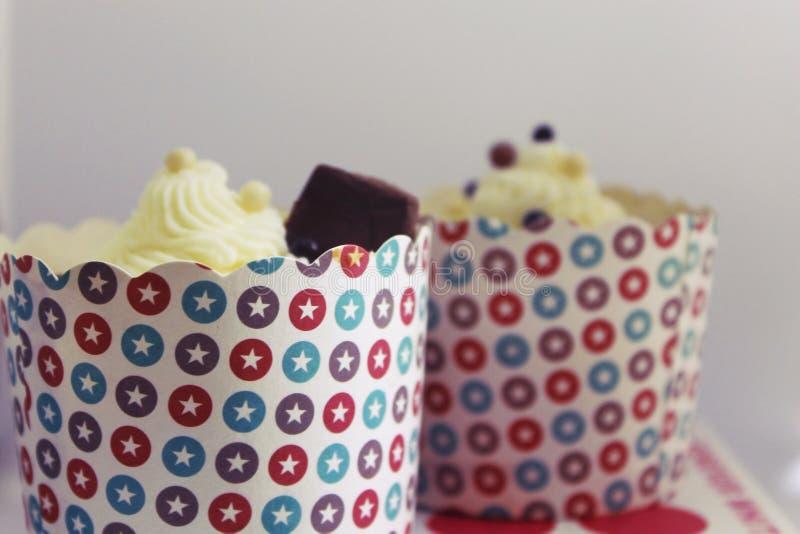 Fyra nya smakliga vaniljmuffin med glasyr på kaka arkivfoto