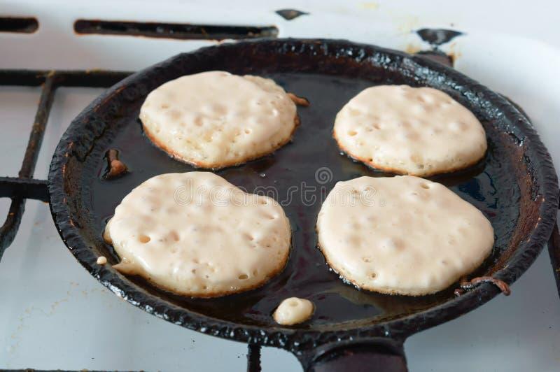 Fyra pannkakor stekte i en panna som lagar mat pannkakor i en panna royaltyfria bilder