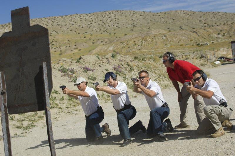 Fyra personer som avfyrar vapen på skjutbana royaltyfri fotografi