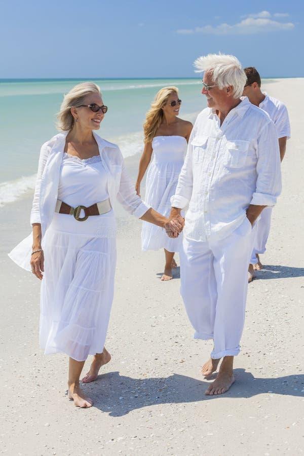 Fyra personer två pensionärfamiljpar som går den tropiska stranden arkivfoton