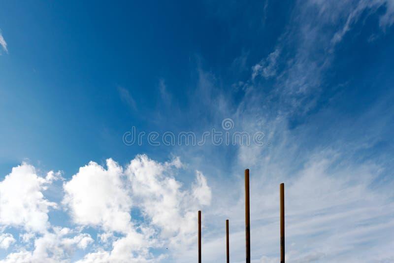 Fyra poler verkar att skjuta i höjden in i en ljus blå molnig himmel fotografering för bildbyråer