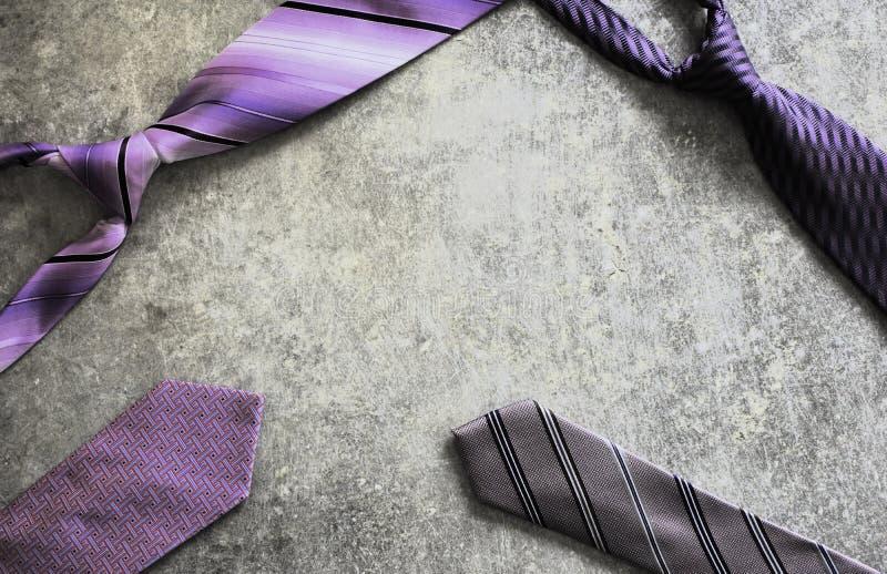 Fyra purpurfärgade violetta mönstrade band på skrapad grå grunge bordlägger bakgrund royaltyfria foton