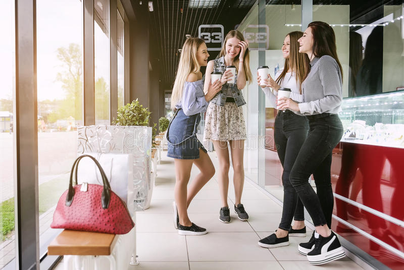 Fyra shoppa flickor talar och skrattar, i gallerian royaltyfria bilder