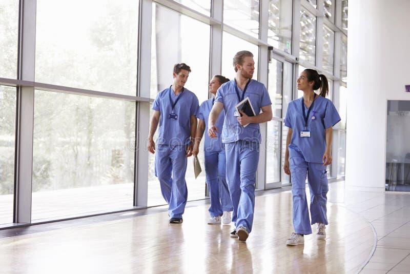 Fyra sjukvårdarbetare skurar in att gå i korridor arkivbild