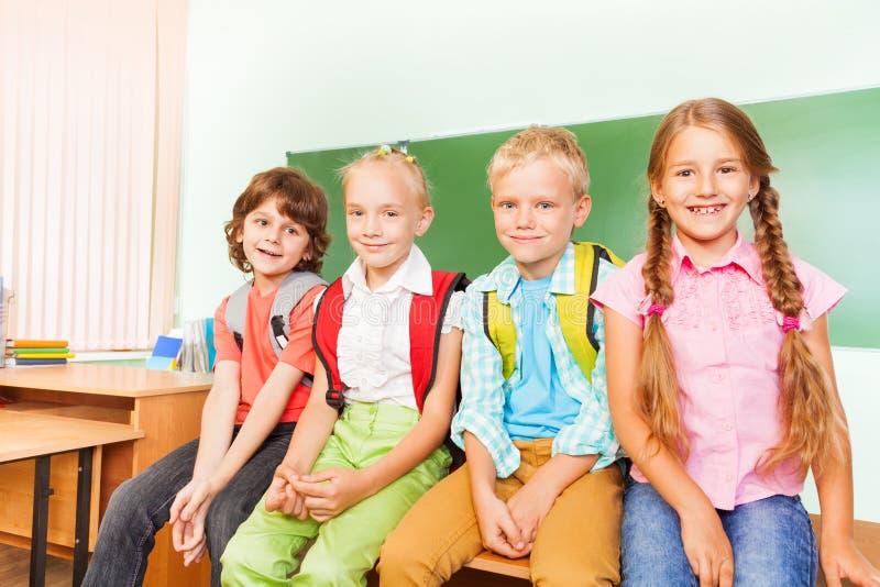 Fyra skolbarn som sitter, i rad och att le royaltyfria bilder