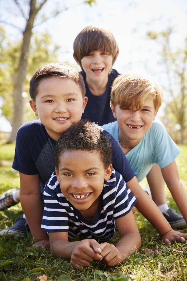 Fyra skolpojkar som ligger på de i en parkera, stående royaltyfria bilder