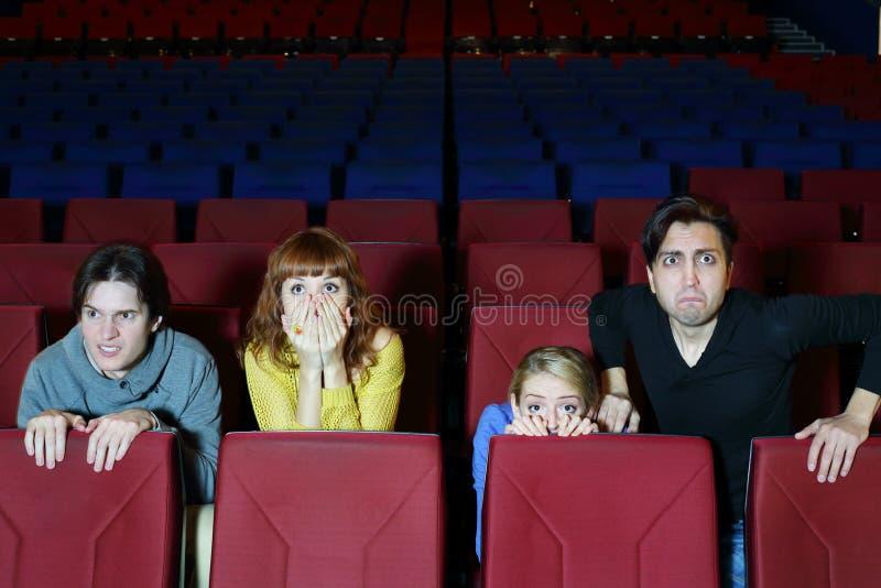 Fyra skrämde vänner ser film i bioteater arkivbild
