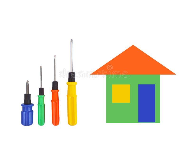 Fyra skruvmejslar av olika format med blått, gräsplan, röda och gula handtag och ett tecknad filmhus av samma färgar, isolerat arkivbild