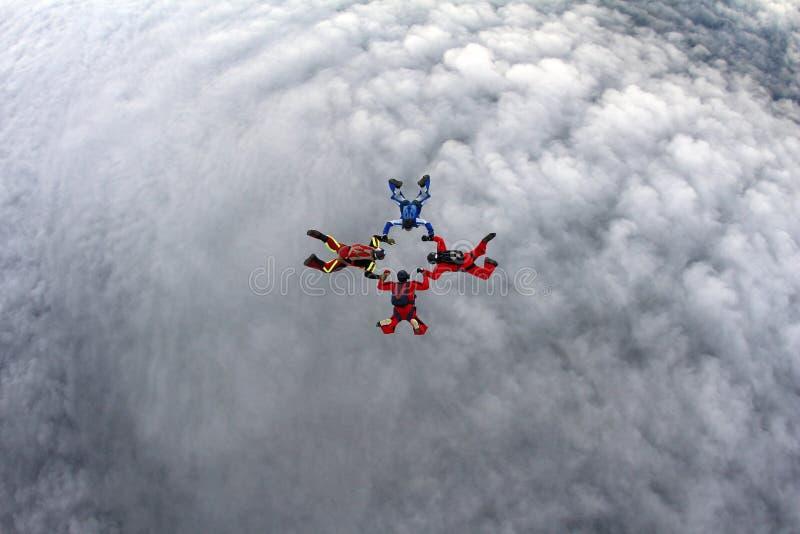 Fyra skydivers är i himlen royaltyfria bilder