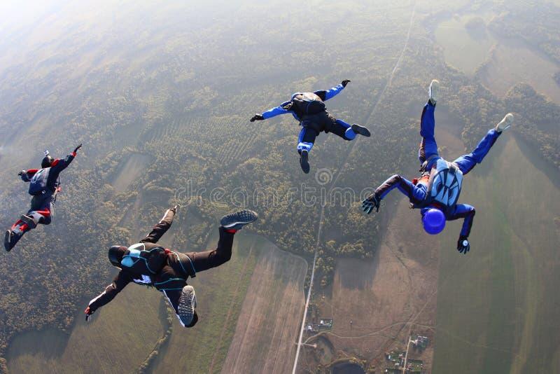Fyra skydivers i himlen royaltyfri fotografi