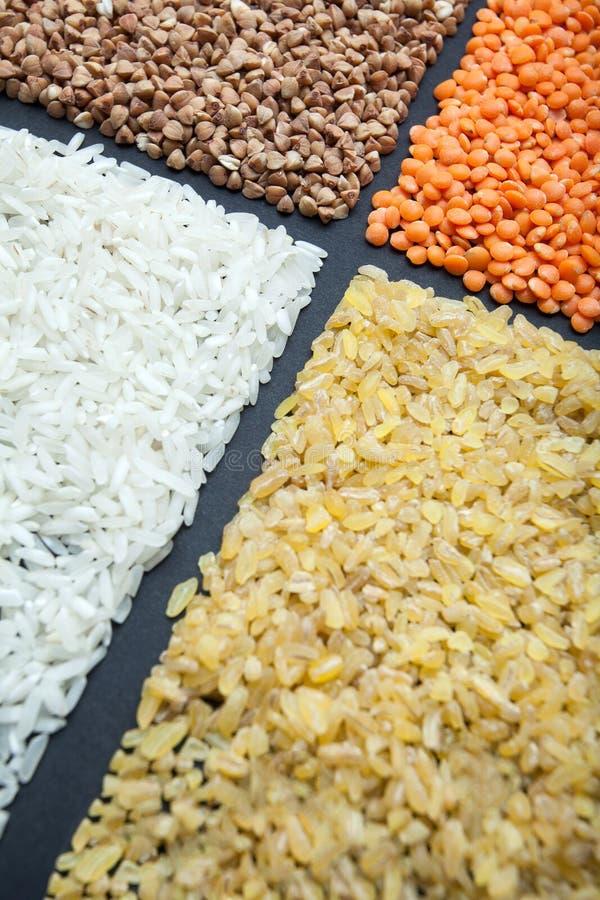 Fyra sorter av organiska sädesslag: ris, bulgur, bovete och linser på en svart bakgrund arkivfoton
