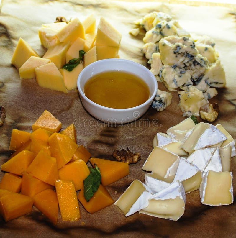 Fyra sorter av ost med honung och br?d arkivfoto