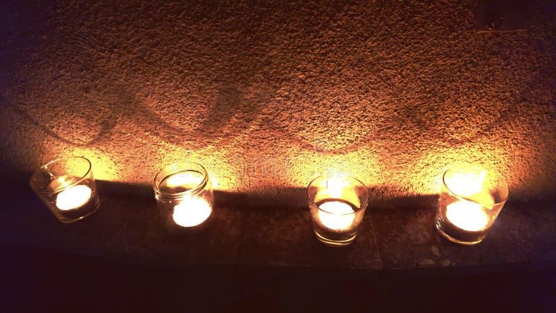 Fyra stearinljus blixt upp väggen arkivfoton
