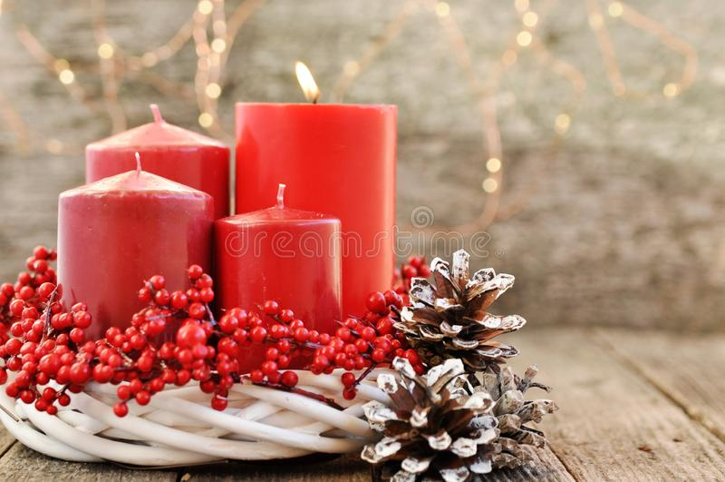 Fyra stearinljus i en vit krans med röda bär på en trälantlig bakgrund med ljus adventkalender för jul royaltyfria foton