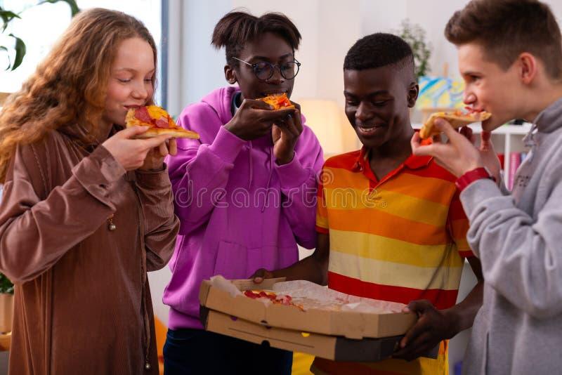 Fyra stilfulla tonåringar som äter läcker pizza efter skola royaltyfria foton