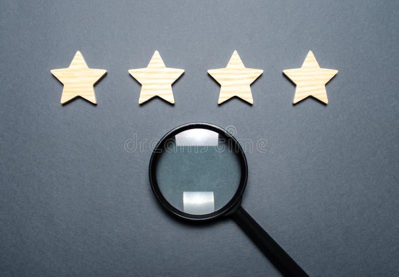 Fyra stjärnor och ett förstoringsglas Värdering av hotell och restauranger, dyra institutioner Berömmelse och unikhet som tilldra arkivbild