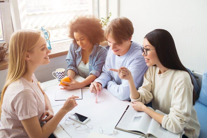 Fyra studenter sitter tillsammans på tabellen och har konversation Den afro- amerikanska flickan rymmer en apelsin och royaltyfri fotografi