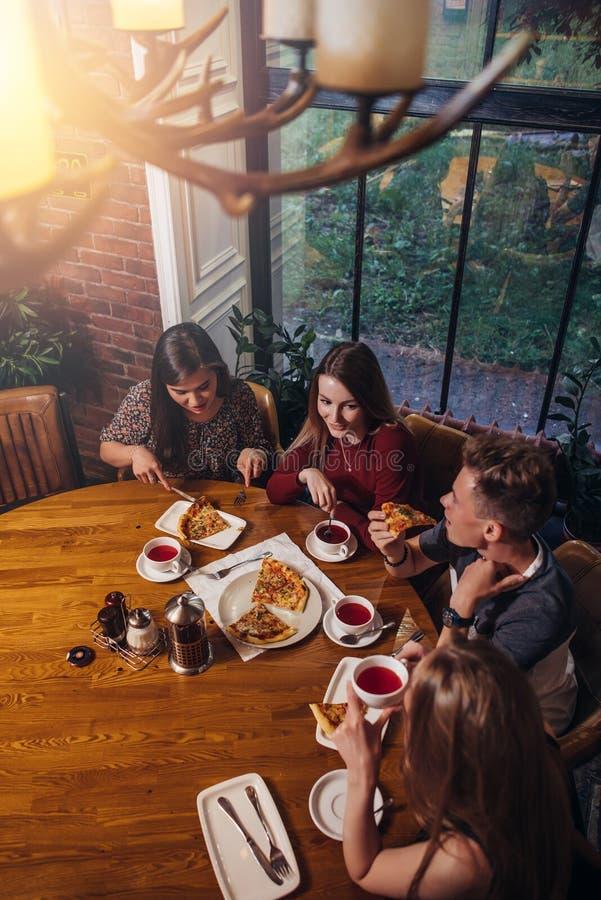 Fyra studenter som tycker om aftonmål som äter pizza som dricker te som pratar i moderiktig restaurang royaltyfri foto