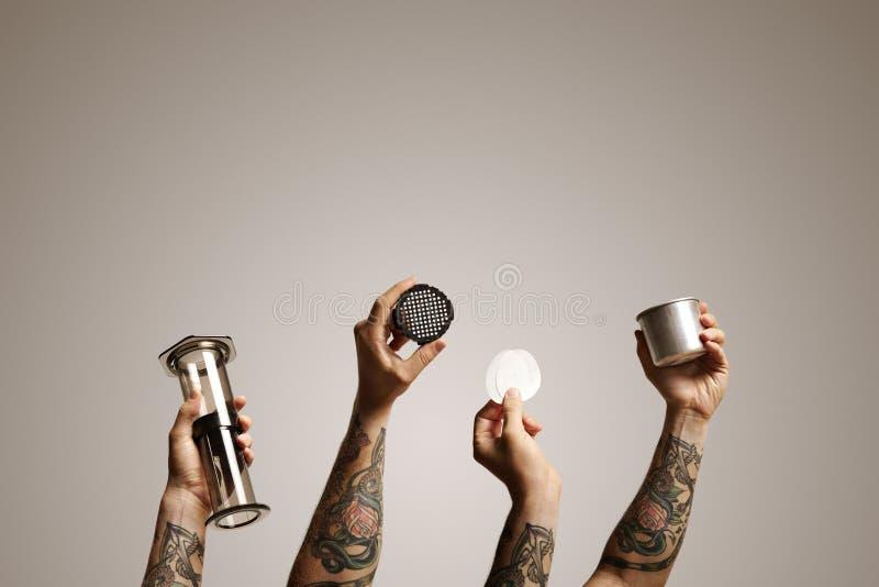 Fyra tatuerade händer som rymmer aeropressdelar fotografering för bildbyråer