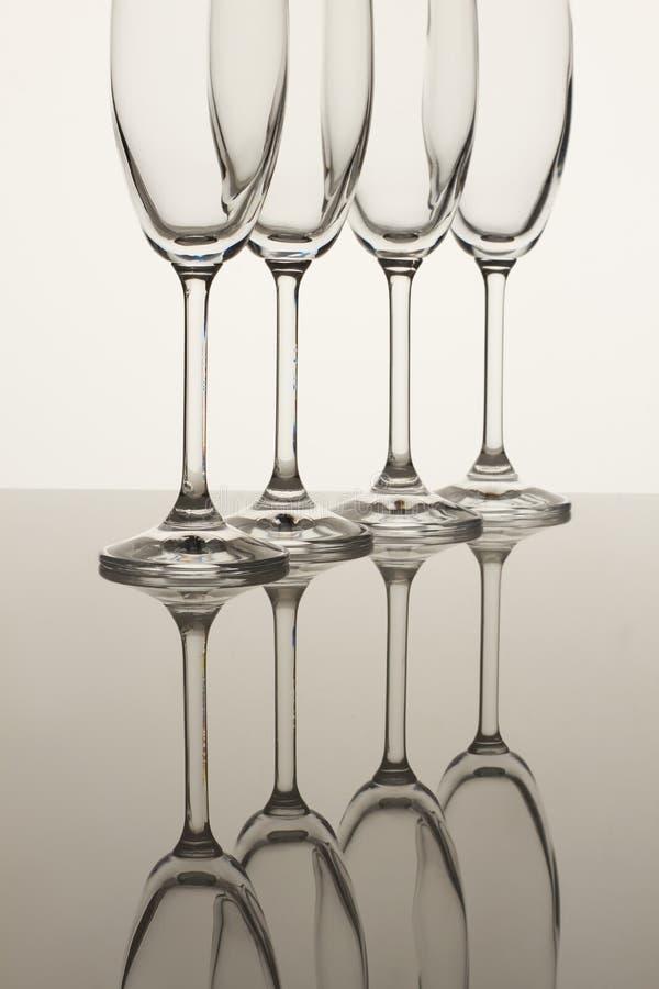 Fyra tomma champagneexponeringsglas på vit arkivfoto