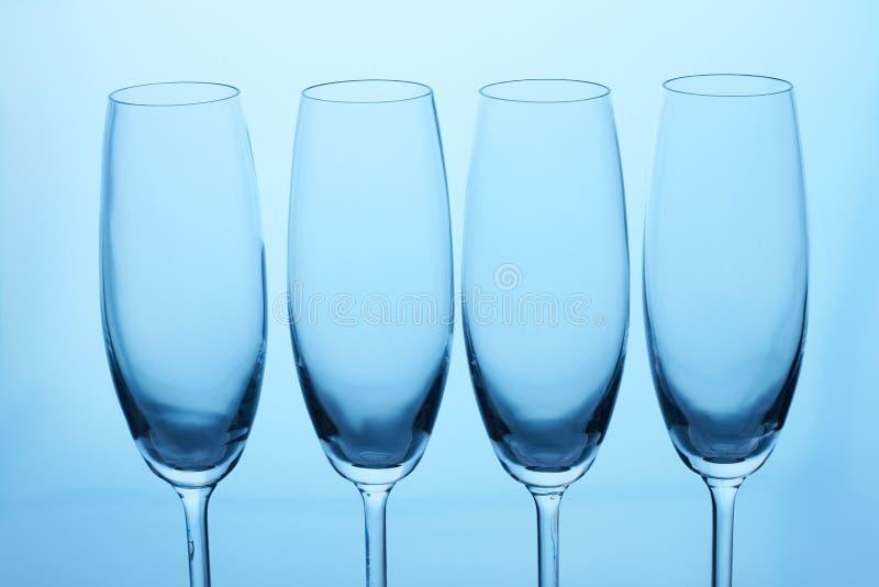 Fyra tomma exponeringsglas för champagne och vin arkivbilder