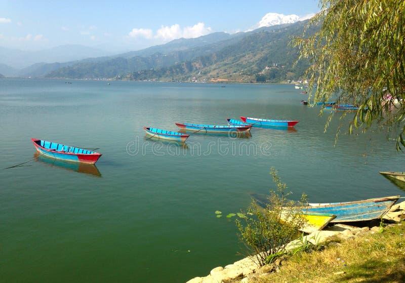 Fyra tomma turist- fartyg på sjön Pheva, bergsikt royaltyfri fotografi
