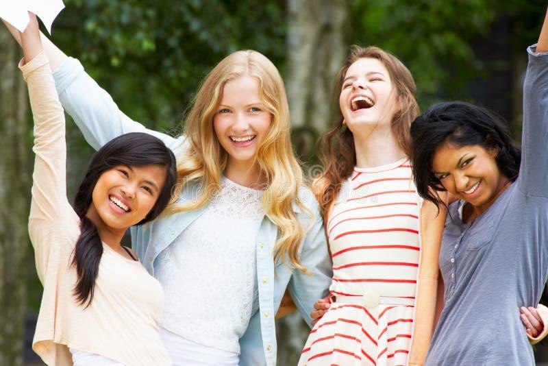 Fyra tonårs- flickor som firar lyckade examenresultat royaltyfria foton