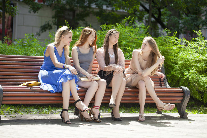 Fyra tonårs- flickor som sitter på bänk i sommar, parkerar royaltyfria foton