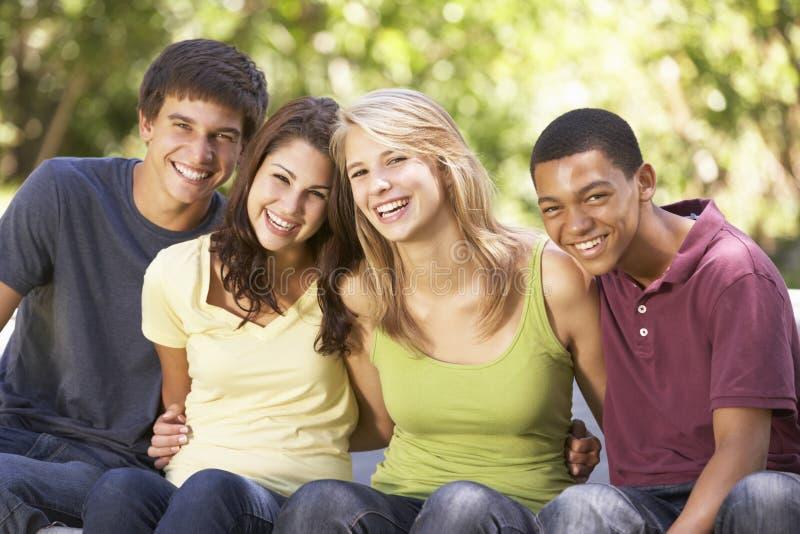 Fyra tonårs- vänner som sitter på trampolinen i trädgård royaltyfria bilder