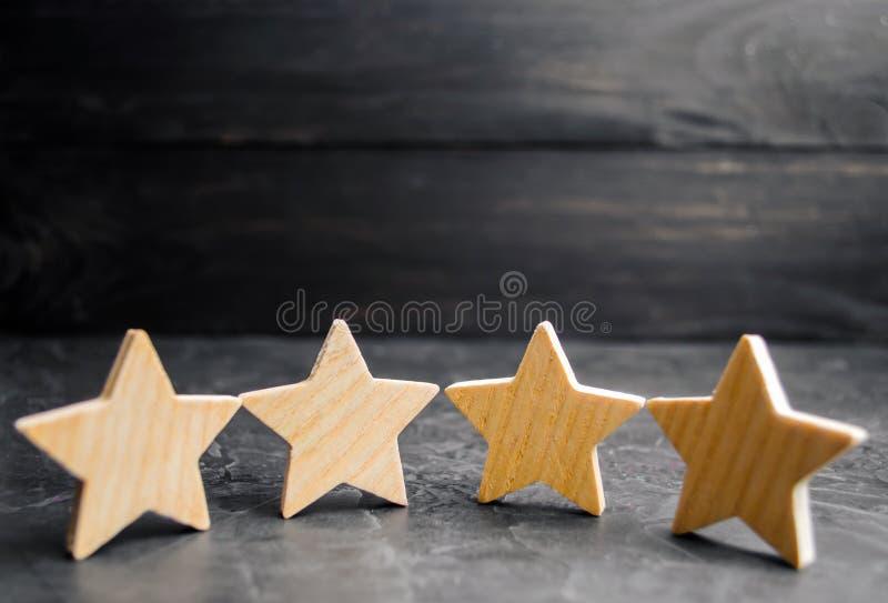Fyra trästjärnor Begreppet av värderingen och utvärderingen Värderingen av hotellet, restaurang, mobil applikation Kvalitets- ser royaltyfri bild