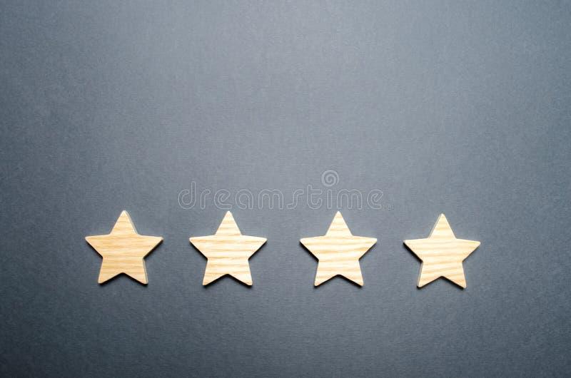 Fyra trästjärnor Begreppet av värderingen och utvärderingen Värderingen av hotellet, restaurang, mobil applikation Kvalitets- ser arkivbild