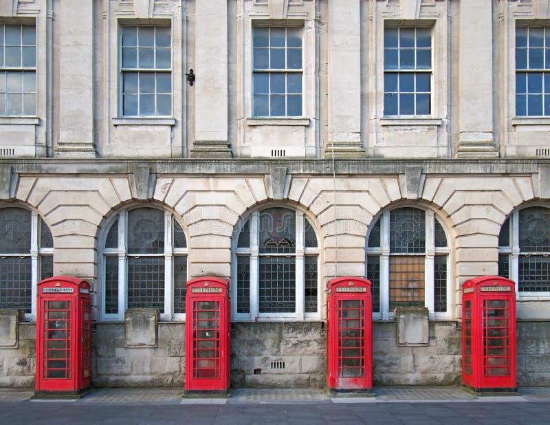 Fyra traditionella brittiska röda telefonaskar utanför en gammal stolpe - kontorsbyggnad i blackpool England royaltyfria foton