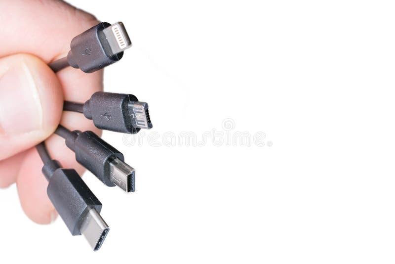 Fyra typer av laddande kablar framme av vit bakgrund med kopieringsutrymme arkivfoto