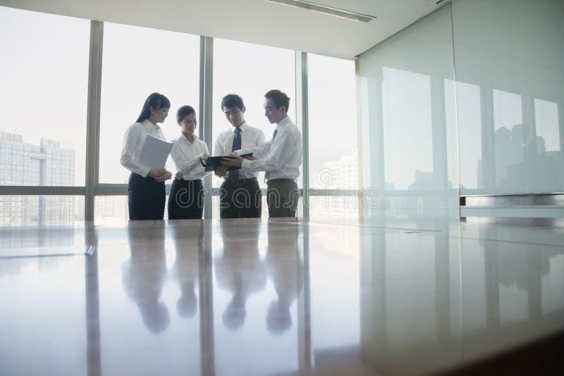 Fyra unga affärspersoner som står vid konferenstabellen arkivfoto