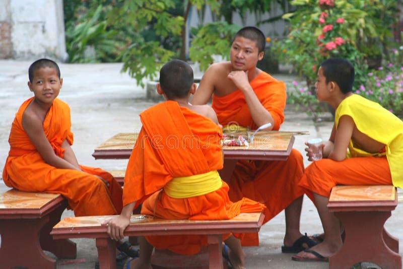 Fyra unga buddistiska munkar i en tempel i Luang Prabang, Laos royaltyfri foto