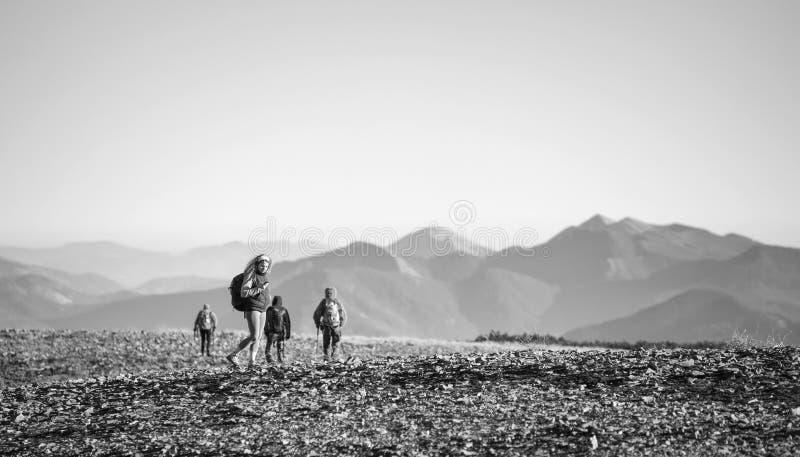 Fyra unga idrotts- personer som går på det steniga berget plato royaltyfri bild