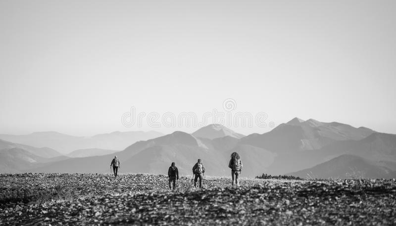 Fyra unga idrotts- personer som går på det steniga berget plato arkivbilder