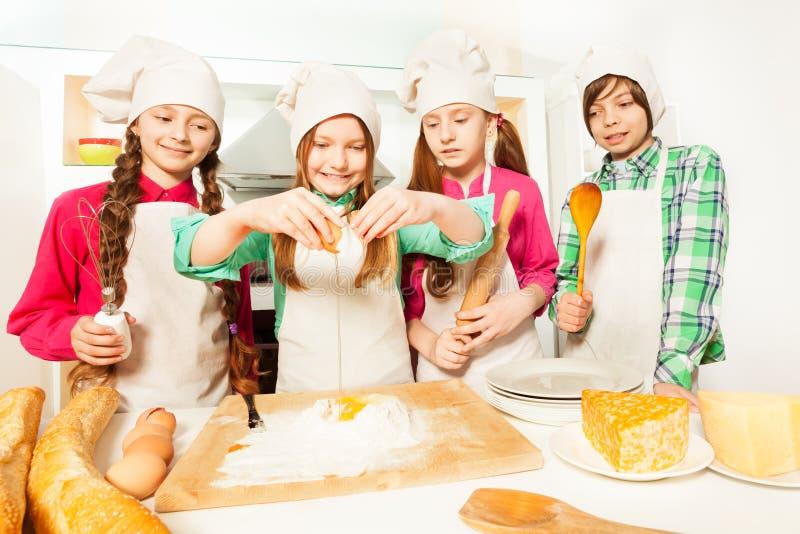 Fyra unga kockar som lär att förbereda bagerideg arkivbild