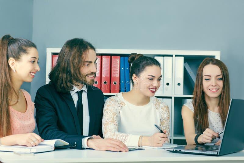 Fyra unga kollegor som tillsammans arbetar i en modern coworking studio Affärspartners som använder bärbara datorn, och diskutera royaltyfri bild