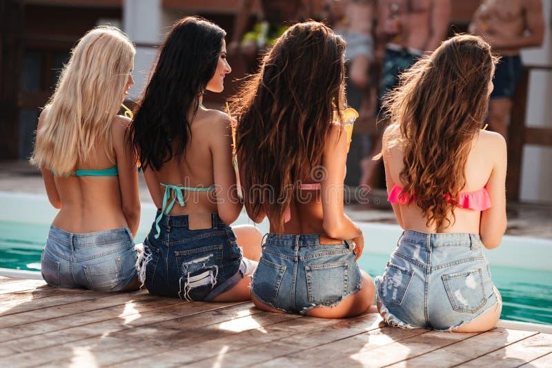 Fyra unga kvinnor med långt hår som sitter nära simbassäng royaltyfri bild